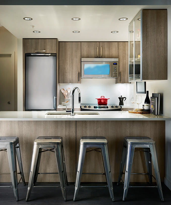 Impressive kitchen finishes including stainless steel appliances, quartz counters and wood grain cabinetry will be standard features at The Heatley Strathcona condos in vancouver.